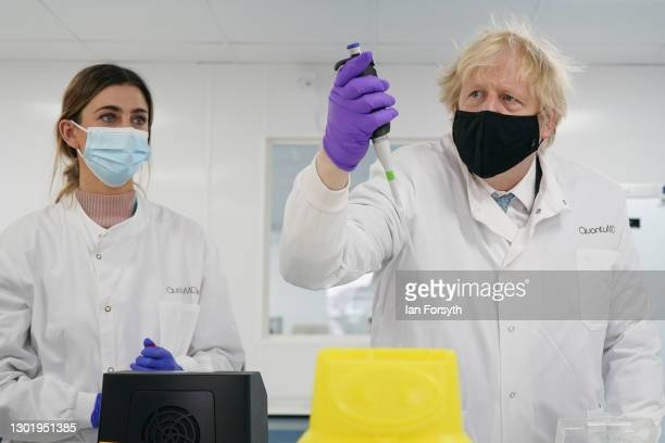 Prime Minister Boris Johnson uses a pipette as he is briefed by a molecular biologist during a visit to the QuantuMDx Biotechnology company in...
