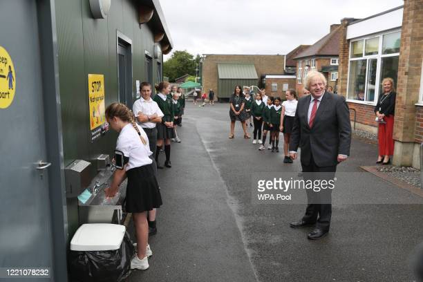 Prime Minister Boris Johnson waits in line in the playground to wash his hands during a visit to Bovingdon Primary School on June 19 2020 near Hemel...