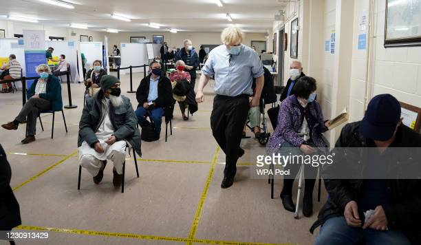 Prime Minister Boris Johnson walks past waiting patients as he visits a COVID-19 vaccination centre in Batley, on February 1, 2021 in West Yorkshire,...