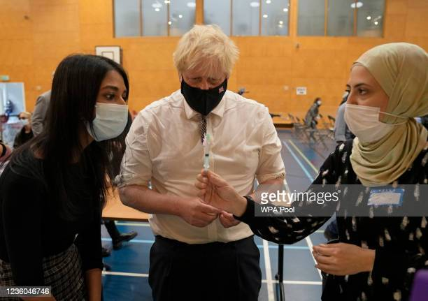 Prime Minister Boris Johnson watches as staff dilute a dose of the pfizer vaccine before administering it as he visits a COVID-19 vaccination centre...