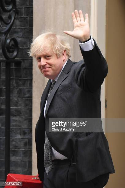 Prime Minister Boris Johnson waves as he returns to Downing Street after attending parliament on December 30, 2020 in London, England. The United...