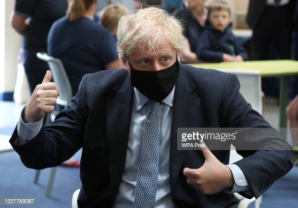 Prime Minister Boris Johnson wears a face mask as he speaks with families in the community centre at RAF Lossiemouth, Moray, during a visit to the...