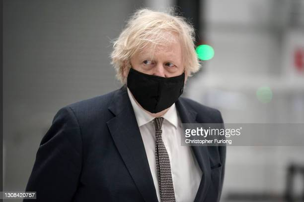 Prime minister Boris Johnson wears a face mask during a visit to BAE Systems at Warton Aerodrome on March 22, 2021 in Preston, England. The prime...