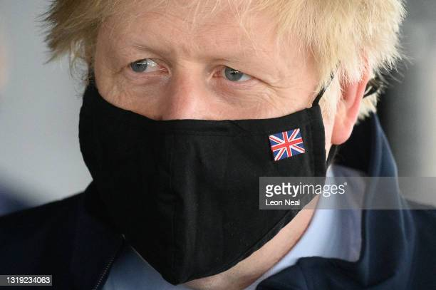 Prime Minister Boris Johnson wears a Union Flag face mask during a visit to HMS Queen Elizabeth aircraft carrier on May 21, 2021 in Portsmouth,...