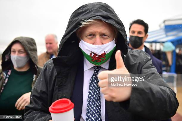 Prime Minister Boris Johnson wears a Welsh flag face mask and gives a thumbs up as he visits Marco's cafe in Barry Island during the Senedd election...