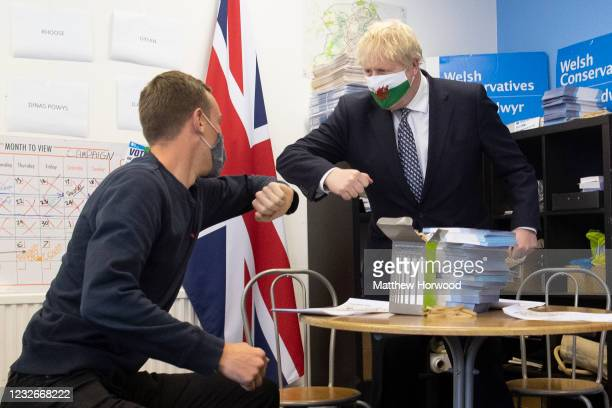 Prime Minister Boris Johnson wears a Welsh flag face mask as he touches elbows with a campaigner during a visit to Barry during the Senedd election...