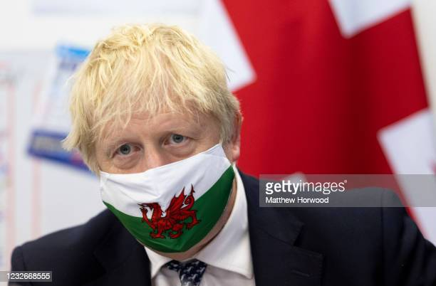 Prime Minister Boris Johnson wears a Welsh flag face mask as he visits Barry during the Senedd election campaign on May 3, 2021 in Vale of Glamorgan,...