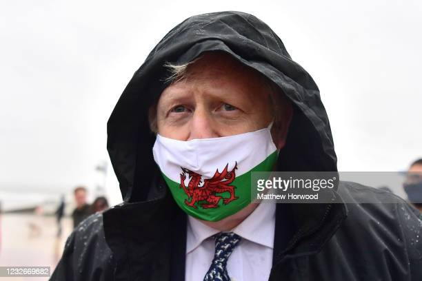 Prime Minister Boris Johnson wears a Welsh flag face mask as he visits Barry Island during the Senedd election campaign on May 3, 2021 in Vale of...