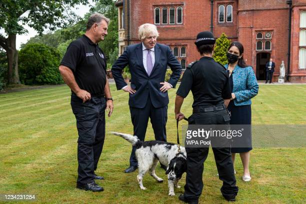 Prime Minister Boris Johnson, with Home Secretary Priti Patel, interact with Pete Greenfield, senior dog instructor and PC Suzanne West with Murphy,...
