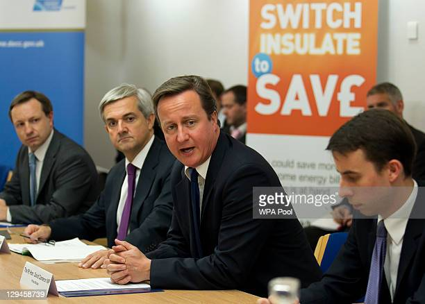 Prime Minister David Cameron addresses a meeting of energy heads flanked by his energy secretary Chris Huhne during a summit on gas and electricity...