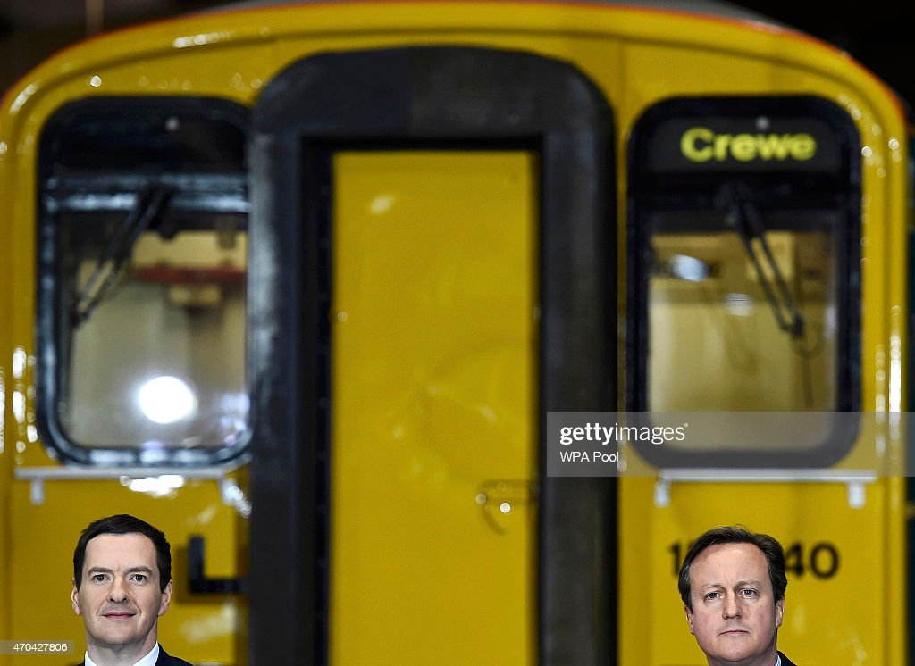 Prime Minister David Cameron (R) and Chancellor of the Exchequer George Osborne address guests during a visit to Arriva TrainCare mantenance plant in Crewe during the fourth week of their election campaign, on April 20, 2015 in Crewe, England. Britain goes to the polls in a General Election on May 7.