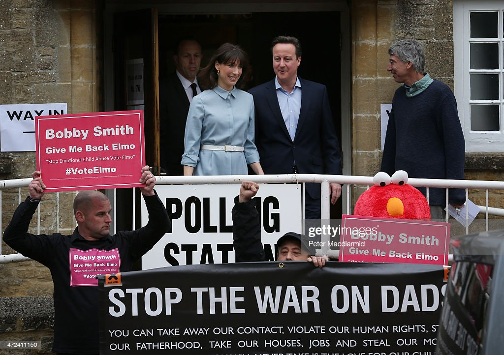Prime Minister David Cameron and his wife Samantha look at demonstrators as they leave a polling station after casting their vote in the general election on May 6, 2015 in Spelsbury, England. The United Kingdom has gone to the polls to vote for a new government in one of the most closely fought General Elections in recent history. With the result too close to call it is anticipated that there will be no overall clear majority winner and a coalition government will have to be formed once again.