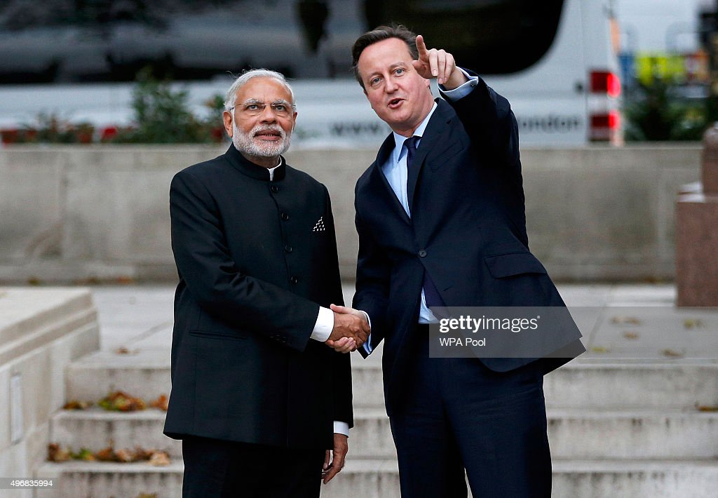 Prime Minister David Cameron and India's Prime Minister Narendra Modi watch a flypast by the Red Arrow RAFD display team next to the statue of Mahatma Ghandi in Parliament Square during an official three day visit on November 12, 2015 in London, England. In his first trip to Britain as Prime Minister Modi's visit will aim to develop economic ties between the two countries. In a busy schedule he is due to speak at Wembley Stadium, have lunch with the Queen at Buckingham Palace, address Parliament and stay overnight at Chequers.