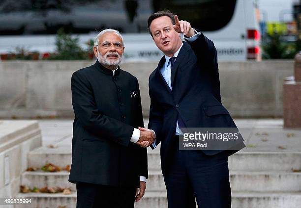 Prime Minister David Cameron and India's Prime Minister Narendra Modi watch a flypast by the Red Arrow RAFD display team next to the statue of...