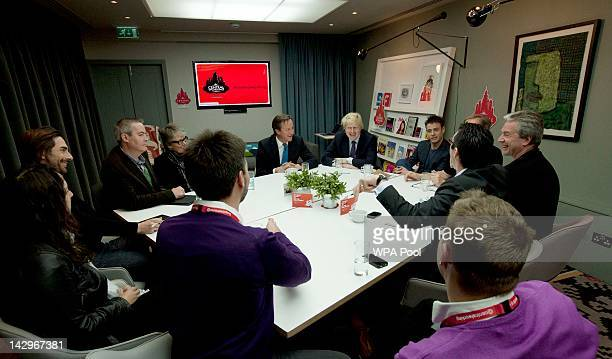 Prime Minister David Cameron and London's Mayor Boris Johnson sit in on a round table discussion with entrepreneurs on April 16 2012 in London...