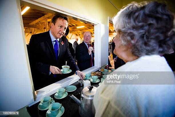 Prime Minister David Cameron and MP Alistair Burt get a cup of tea from party volunteer Anne Harper during their visit to The Women's Institute on...