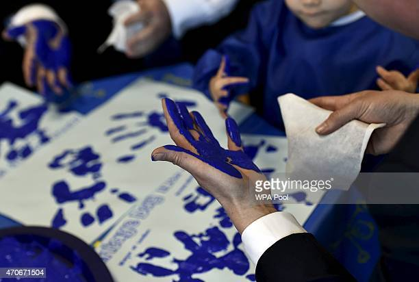 Prime Minister David Cameron cleans his hands during a handprinting session with children at the Advantage children's daycare nursery on April 22...
