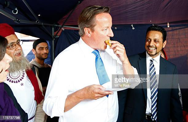Prime Minister David Cameron eats a samosa during a visit to the Jamia Mosque on August 7 2013 in Manchester England Cameron reportedly also called...
