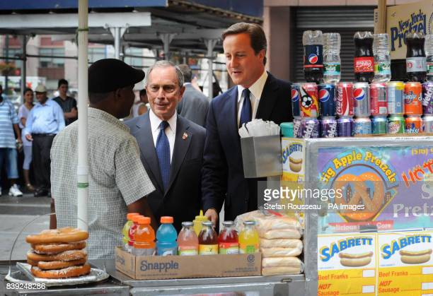 Prime Minister David Cameron enjoys a hotdog with New York City Mayor Michael Bloomberg as he arrived at Penn Station from Washington DC today as...