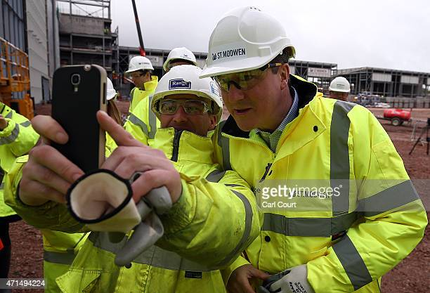 Prime Minister David Cameron has a selfie photograph taken with a builder as he visits Longbridge redevelopment site on April 29 2015 in Birmingham...