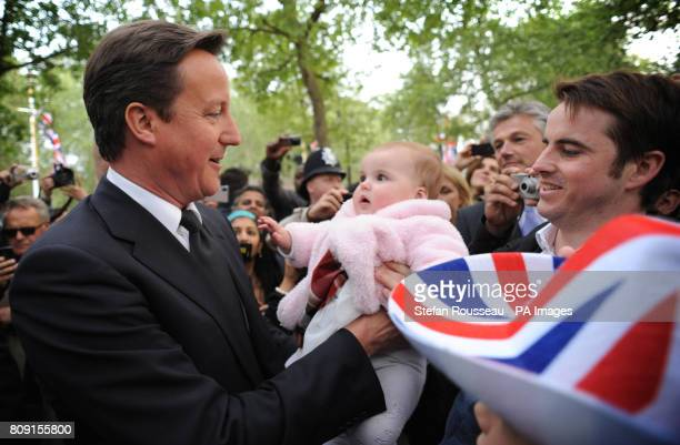 Prime Minister David Cameron holds a baby during a walk along The Mall this evening to meet royal well wishers and to revisit the spot he camped out...