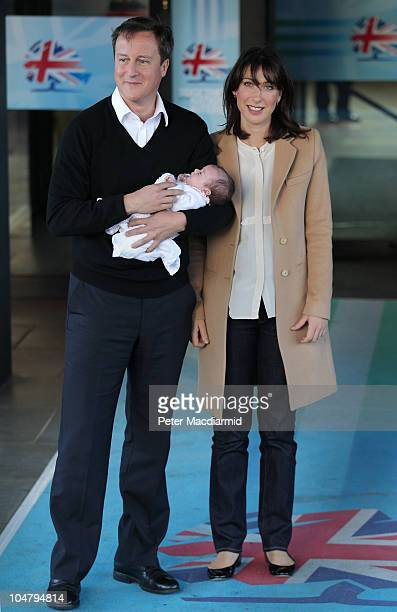 Prime Minister David Cameron holds his baby daughter Florence as he arrives at the Conservative Party Conference with his wife Samantha on October 5...