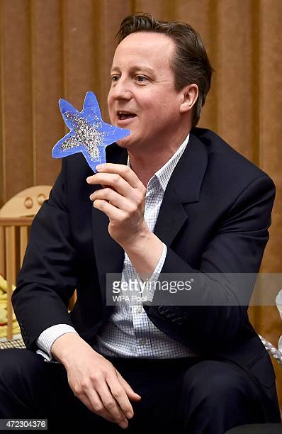 Prime Minister David Cameron holds up a blue star given to him by a child during a campaign visit to a nursery on May 6 2015 in Cannock United...