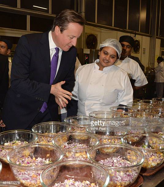 Prime Minister David Cameron inspects the kitchen and meets the chefs at the British curry awards at Battersea Evolution on November 25 2013 in...