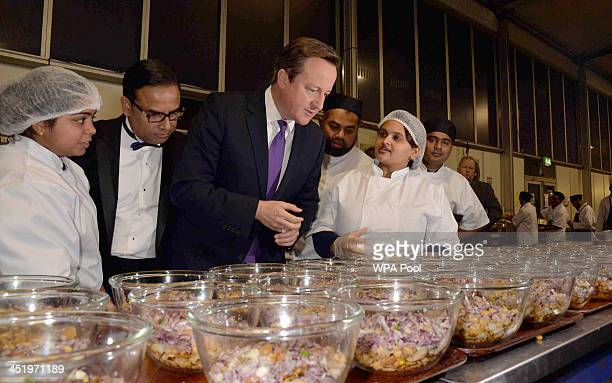 Prime Minister David Cameron inspects the kitchen with Enam Ali founder of awardwinning restaurant Le Raj The British Curry Awards and Spice Business...