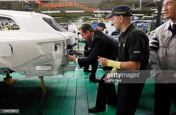Prime Minister David Cameron installs a badge on a car at a Toyota plant on November 24 2011 in Burnaston United Kingdom Toyota will invest 265...