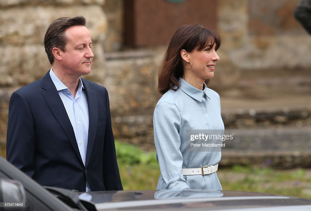 Prime Minister David Cameron is led by his wife Samantha as they leave a polling station after casting their vote in the general election on May 6, 2015 in Spelsbury, England. The United Kingdom has gone to the polls to vote for a new government in one of the most closely fought General Elections in recent history. With the result too close to call it is anticipated that there will be no overall clear majority winner and a coalition government will have to be formed once again.