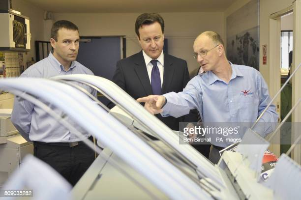 Prime Minister David Cameron is shown a specialist printer by First 4 Numbers graphic designer Richard Barrett with Director, Darren Powell at the...