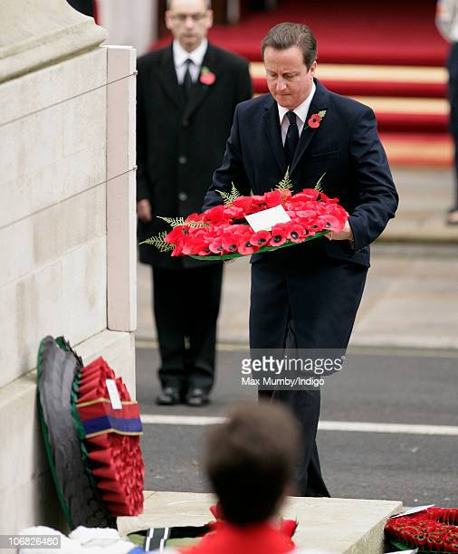 Prime Minister David Cameron lays a wreath of poppies as he attends the annual Remembrance Sunday service at the Cenotaph on November 14, 2010 in...