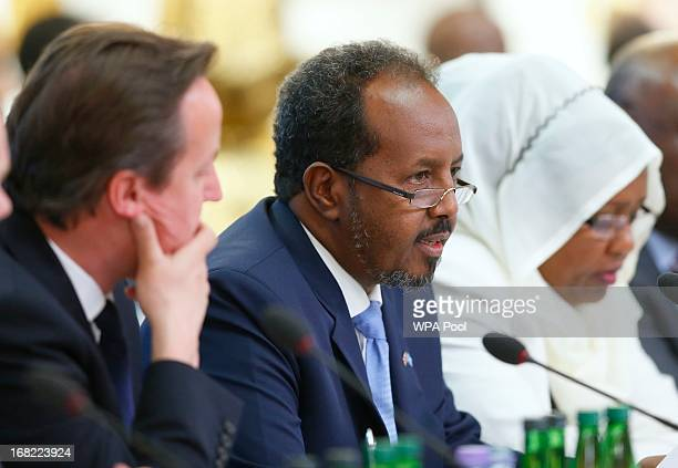 Prime Minister David Cameron listens as Somali President Hassan Sheikh Mohamud speaks during the Somali conference on May 7 2013 in London England...
