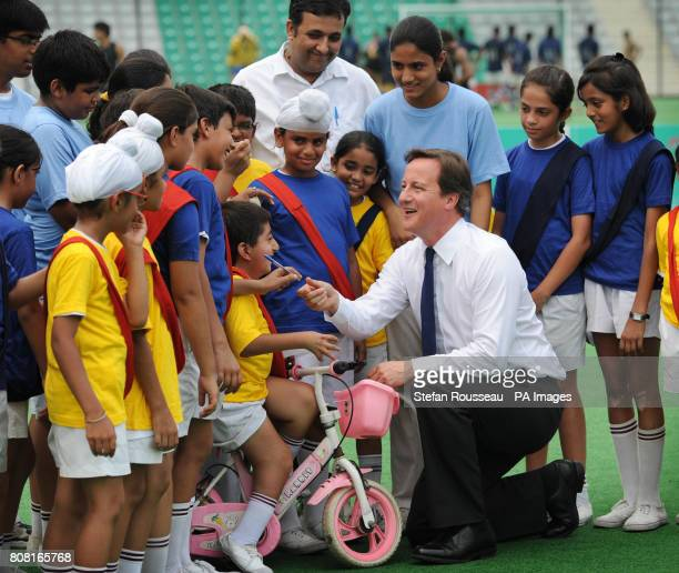 Prime Minister David Cameron meets local school children at the Major Dhyan Chand National Hockey Stadium in Delhi on the last day of a three day...