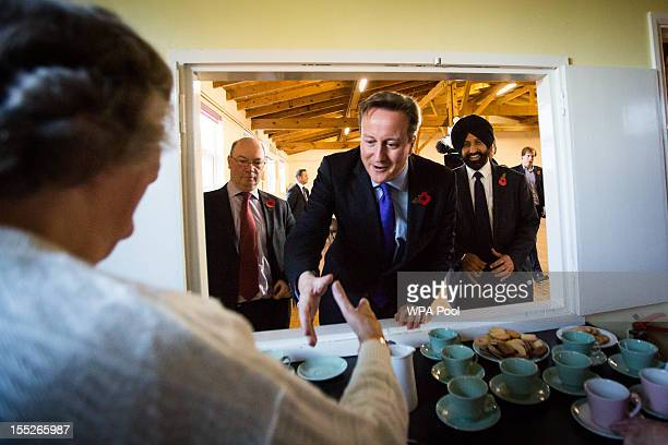 Prime Minister David Cameron meets party volunteer Anne Harper as MP Alistair Burt and Conservative Party PCC candidate Jas Parmar look on during...
