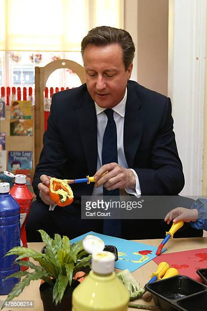 Prime Minister David Cameron paints with vegetables during a visit to a children's nursery on June 1 2015 in London England The new Childcare Bill...