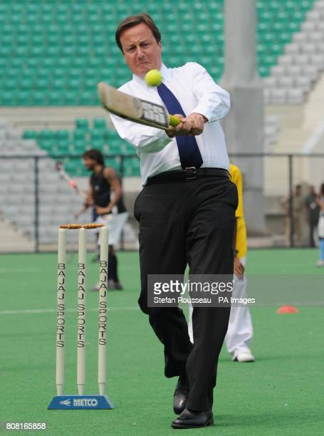Prime Minister David Cameron plays cricket with local school children at the Major Dhyan Chand National Hockey Stadium in Delhi on the last day of a...