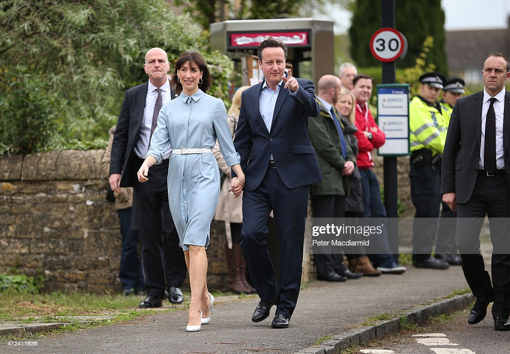 Prime Minister David Cameron points as she walks with his wife Samantha arriving at a polling station to cast their vote in the general election on May 6, 2015 in Spelsbury, England. The United Kingdom has gone to the polls to vote for a new government in one of the most closely fought General Elections in recent history. With the result too close to call it is anticipated that there will be no overall clear majority winner and a coalition government will have to be formed once again.