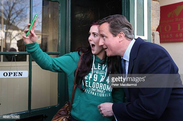 Prime Minister David Cameron poses for a selfie photo with a local woman as he campaigns on April 13 2015 in Alnwick England As the general election...