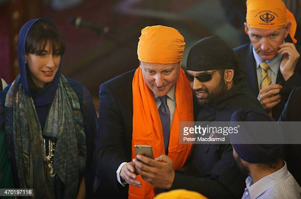 Prime Minister David Cameron poses for a selfie with a worshipper as Samantha Cameron looks on during the Vaisakhi Festival at Guru Nanak Darbar...