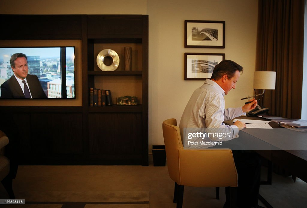Prime Minister David Cameron prepares his keynote speech in his hotel room at the Conservative party conference as his image appears on a TV news broadcast (L) on September 30, 2014 in Birmingham, England. Tomorrow is the final day of conference.