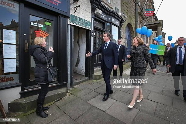 Prime Minister David Cameron reaches out to shake a local women's hand as he campaigns with parliamentary candidate AnneMarie Trevelyan on April 13...
