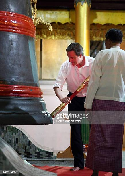 Prime Minister David Cameron rings a bell at the Shwedagon pagoda after meeting with prodemocracy leader Aung San Suu Kyi on April 13 2012 in Yangon...