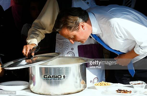 Prime Minister David Cameron smells food during a visit to the Jamia Mosque on August 7 2013 in Manchester England Cameron reportedly also called the...