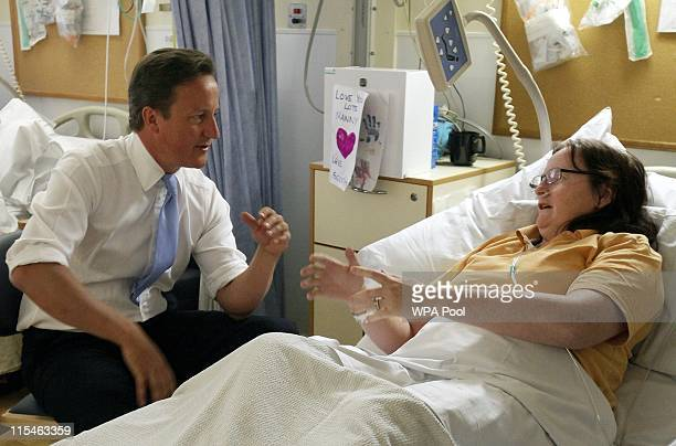 Prime Minister David Cameron speaks to patient Jackie ReidWard during a visit to her ward at University College Hospital before making a speech about...