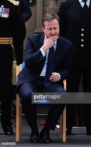 Prime Minister David Cameron speaks with a military officer as he watches the main military parade during the Armed Forces Day National Event on June...