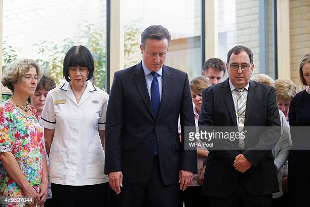 Prime Minister David Cameron stands for a minute's silence with staff members during a visit to Chipping Norton Health Centre in his constituency of...