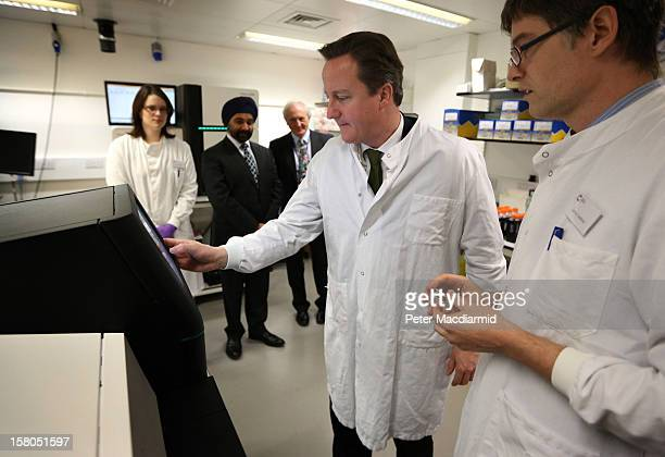 Prime Minister David Cameron stands with Dr James Hadfield as he uses a personal genome sequencing machine at the Cancer Research UK Cambridge...
