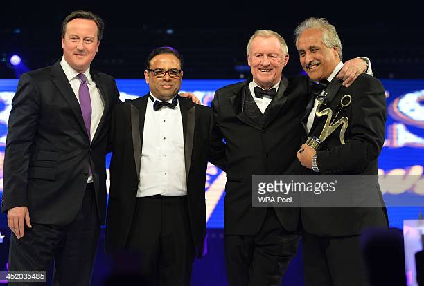 Prime Minister David Cameron stands with Enam Ali host Chris Tarrant and Mohammad Aslam attend the British curry awards at Battersea Evolution on...
